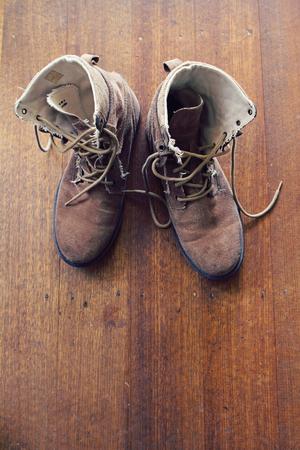 undone: Overhead of worn old walking or work boots on rustic wooden floor