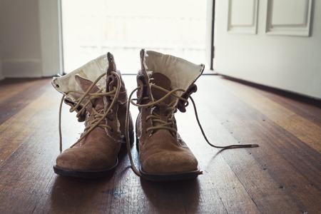 Pair of men's worn leather boots in doorway of home on rustic wooden floorboards