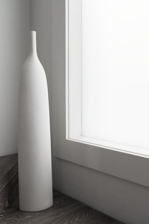 decorative design: Large white vase ornament sculpture next to large window in a luxury home