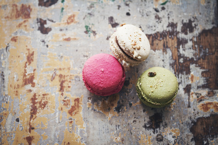 overhead view: Still life of three macarons on rustic background table overhead view Stock Photo
