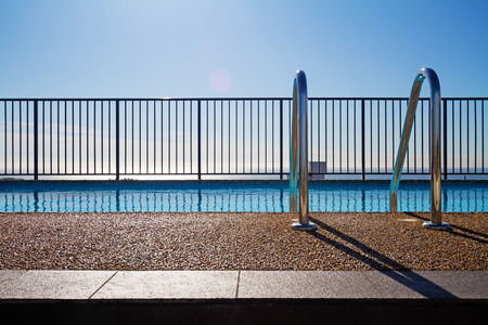 Swimming pool edge with ladder, fence and sky background Stock Photo