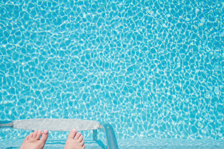 crystal clear: Feet about to climb down ladder into a crystal clear sparkling pool