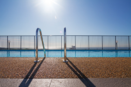 Edge of swimming pool and ladder with sun flare in background