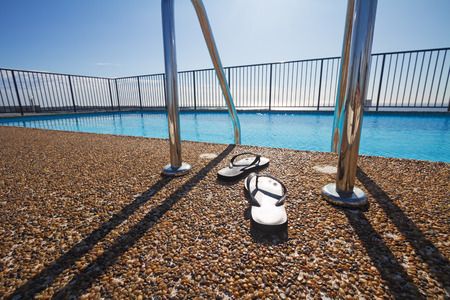 mid century: Flip flops at a pool edge nobody with sun behind Stock Photo