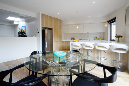 kitchen island: Kitchen with island bench and open plan dining area in modern australian home