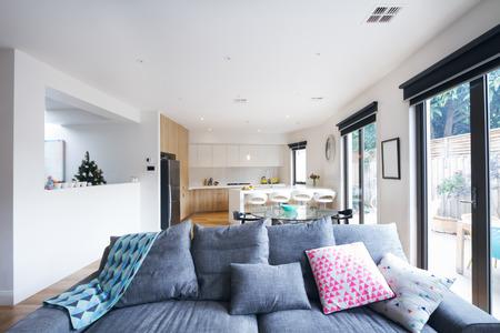 現代的な家のオープン プランのリビング ルームで快適なグレーのソファー