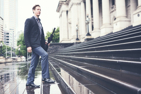 going: Young business man climbing steps on way to work holding umbrella horizontal Stock Photo