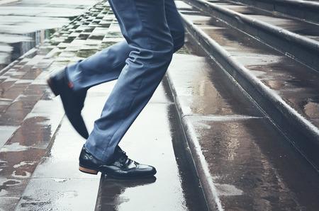 Man legs in suit running late up steps in rain 写真素材