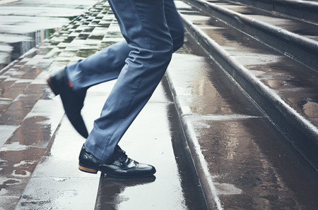 running late: Man legs in suit running late up steps in rain Stock Photo