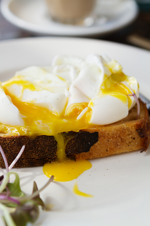 mouth watering: Close up of mouth watering poached egg yolk dripping down toast