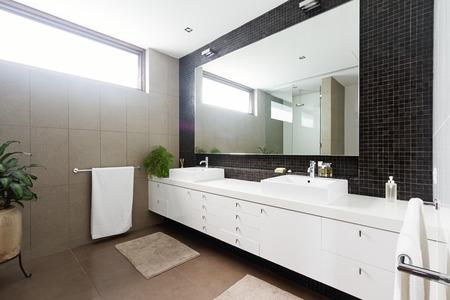 Black mosaic betegelde spatscherm en dubbele wastafel badkamer en suite Stockfoto
