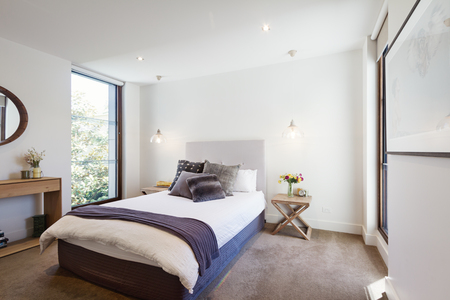 Luxury interior designed bedroom with comfy pillows and throw rug and pendant lights Archivio Fotografico