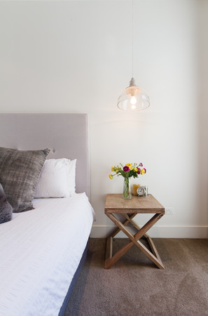 Hamptons styled bedside table with hanging pendant light in luxury home interior Reklamní fotografie