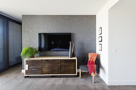 wall decor: Wall mounted tv and buffet in spacious master bedroom with decor items