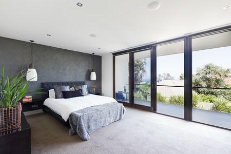glass door: Spacious interior of designer master bedroom in luxury contemporary Australian home