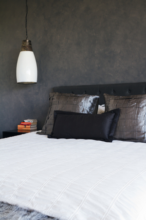 feature wall: Masculine bedroom decor with dark grey painted feature wall and rustic pendant hanging light Stock Photo