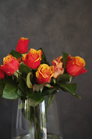 flowers in vase: Close up of orange and yellow roses in glass vase in home interior decor
