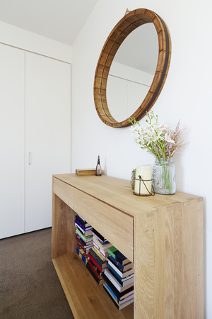 Interior decoration styling of wooden sideboard buffet and mirror with candle and vase of flowers