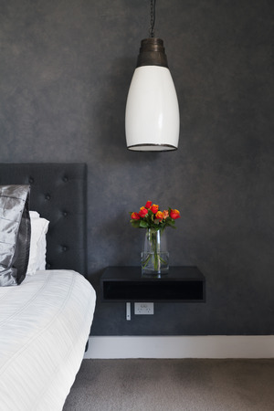 'bedside table': Orange roses on bedside table in contemporary dark bedroom design with pendant lighting Stock Photo