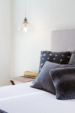 Luksusowe sypialnie z ciemnoszarymi poduszkami i nocnymi lampkami