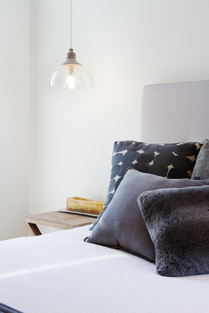 Luxury bedroom details of dark grey throw pillows and bedside penant light