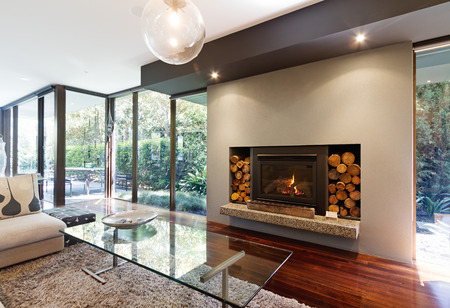 home lighting: Blazing fire in living room of luxury architect designed Australian house Stock Photo