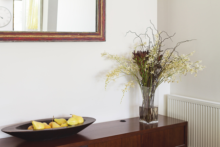 vase: Interior decorator items flowers buffet and mirror in luxury Australian home