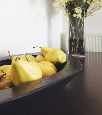 home accents: Close up of yellow pear decorations in a rustic wooden bowl interior designed home Stock Photo