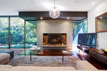 Warm Australische woonkamer met open haard in de hedendaagse luxe huis Stockfoto