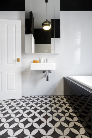 Luxury monochrome designer bathroom renovation with patterned floor tiles
