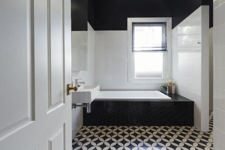 powder room: Designer bathroom renovation with black and white floor tiles horizontal
