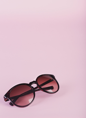 sunnies: Pair of womens sunglasses on sparse pastel pink background