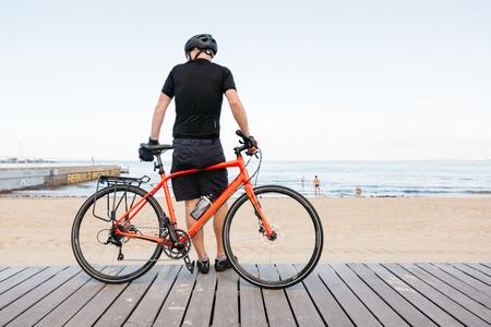 st kilda: Male bike rider leaning against bike viewing the beach Stock Photo