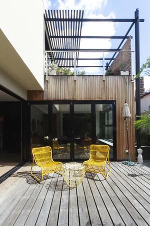 Pár žluté třtiny venkovní židle na dřevěnou podlahu v současném dvoře
