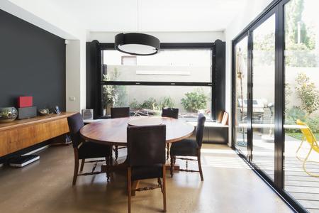 Familia extensión comedor con grandes ventanas de cristal y puertas en la casa contemporánea australiana