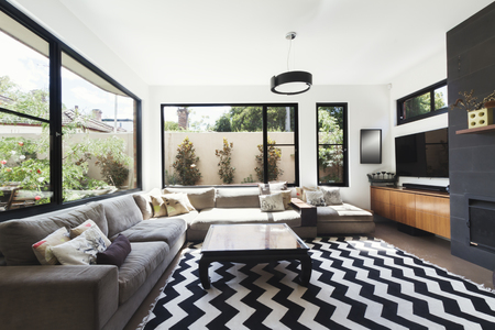 room accents: Black and white scheme living room with wood and grey tiling accents and chevron pattern floor rug