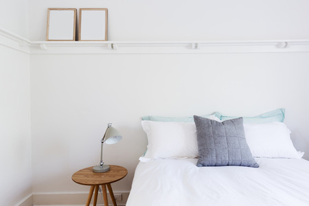 White bedroom with simple decor items in beach styled home apartment