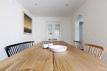 Close up of Danish styled dining room table and chairs in renovated apartment