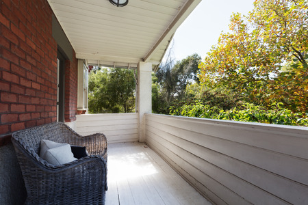 townhome: Spacious apartment balcony with view to the tree tops from cane wicker seat