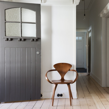 silla de madera: Una decoración sencilla silla de madera de clásico en la entrada renovada plaza de apartamentos Foto de archivo