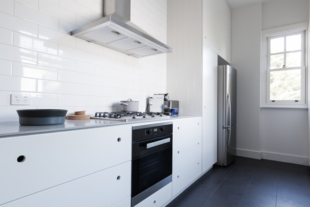 cupboards: Monochrome clean white kitchen benchtop and cupboards with appliances