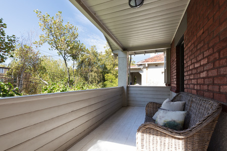 townhome: Large apartment balcony with cane outdoor seating and wood panelling