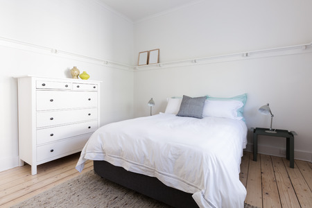 White bedroom with decorator home ware items in beach styled home apartment