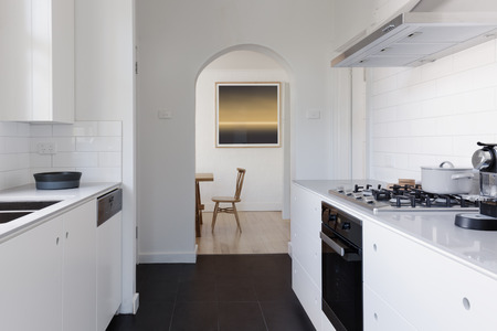 galley: View of dining room at the end of a contemporary white galley apartment kitchen