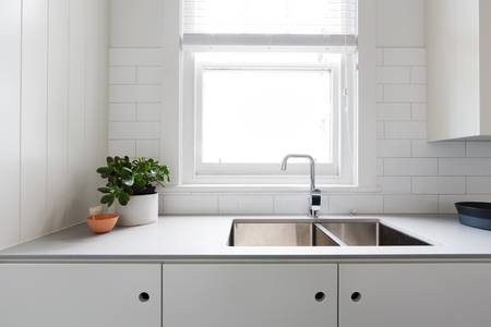 galley: Close up details of contemporary white apartment kitchen with subway tiles