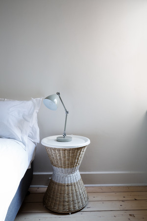 home accent: Close up details of bedside table with lamp and copy space Stock Photo