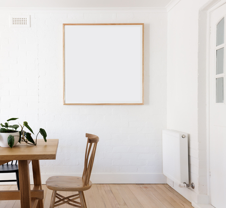 Blank framed print on white wall in beautiful danish styled interior dining room