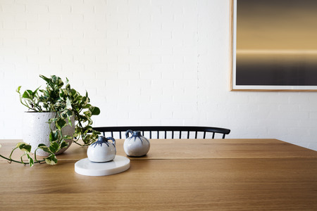Ivy pot plant on table and white brick wall in dining room