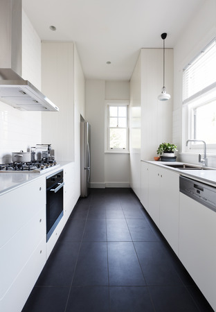 Vertical of a long galley style monochrome newly renovated kitchen