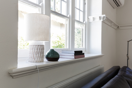 Close up details of lamp books and ornament objects on window sill